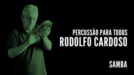 """Rodolfo Cardoso segura seu tamborim com o título """"Percussão para todos - Rodolfo Cardoso - Samba"""""""